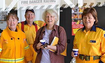 Older female with cup in hand attending a community event held by Rural Fire Brigade