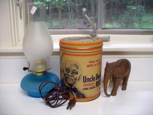 ビンテージっぽいテーブルランプとブリキ缶容器、それと木彫りの象さんの置物。