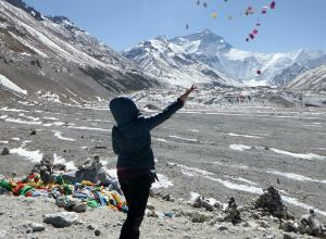Throwing prayer flags in the air for good luck before Mt. Everest in Tibet.