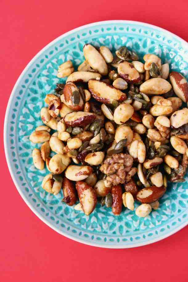 Photo of caramelised nuts on a green plate against a red background