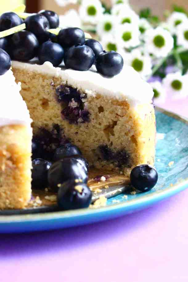Photo of a sponge cake topped with white frosting and fresh blueberries with a slice taken out of it shot from the side