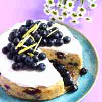 Photo of a sponge cake topped with white frosting and fresh blueberries on a purple background