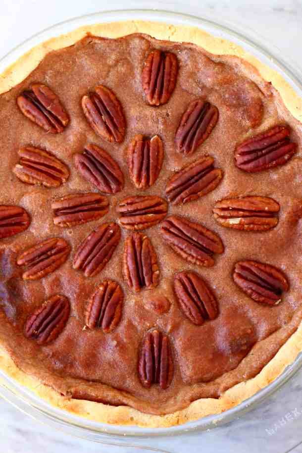 Photo of a brown pie topped with pecan nuts in a glass pie dish against a marble background