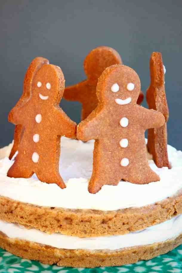 Photo of gingerbread sponge cake sandwiched with white cream topped with five gingerbread men cookies standing in a circle