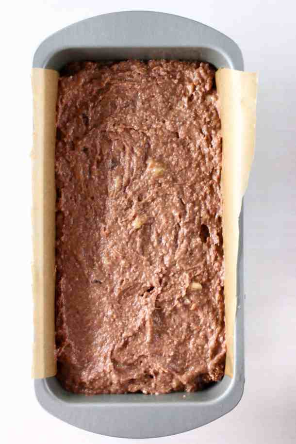 Raw chocolate banana bread batter in a silver loaf tin lined with brown baking paper against a white background