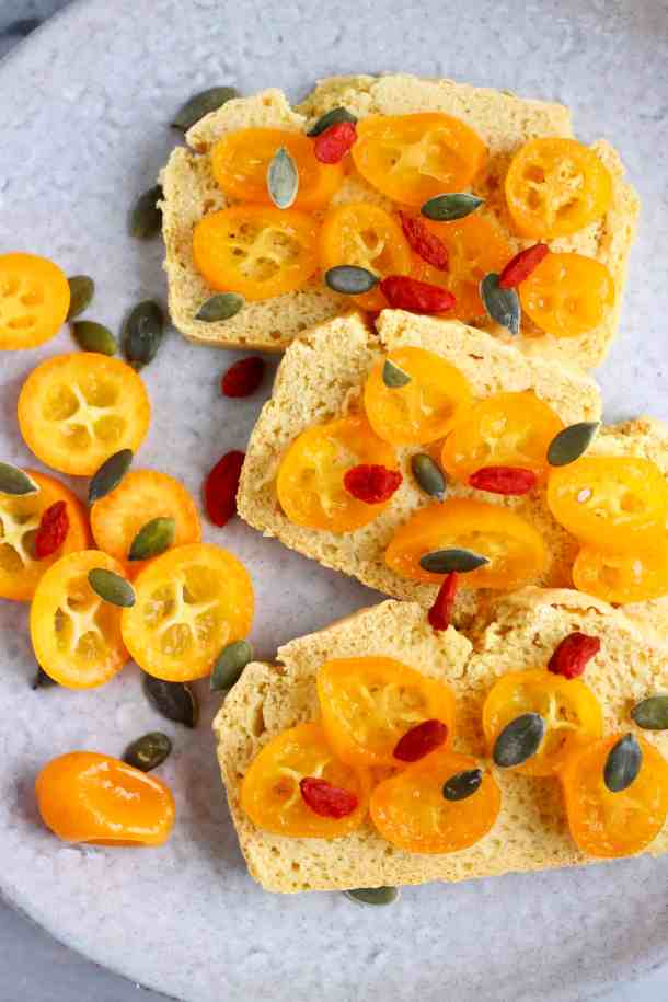 3 slices of bread topped with sliced kumquats, goji berries and pumpkin seeds on a grey plate
