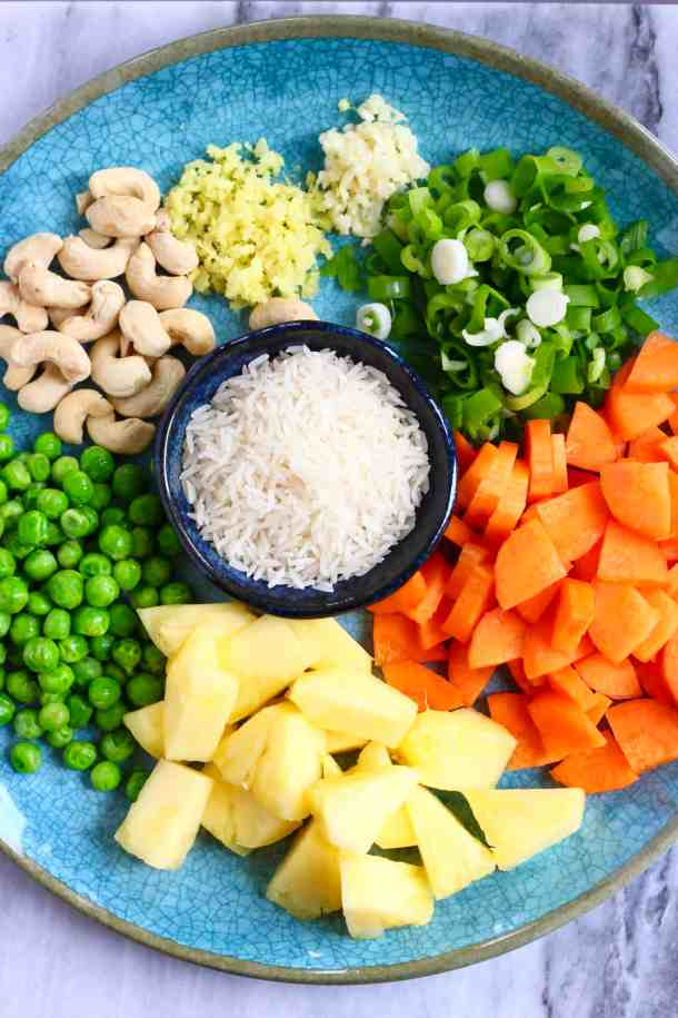 Photo of minced ginger, garlic, sliced spring onions, cashew nuts, green peas, diced carrots, pineapple chunks and raw rice on a blue plate against a marble background
