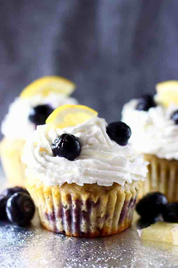 Photo of three blueberry cupcakes topped with white creamy frosting and a fresh blueberry and lemon wedge against a grey background