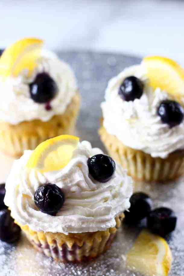 Photo of three cupcakes topped with white creamy frosting, fresh blueberries and lemon wedges on a silver background