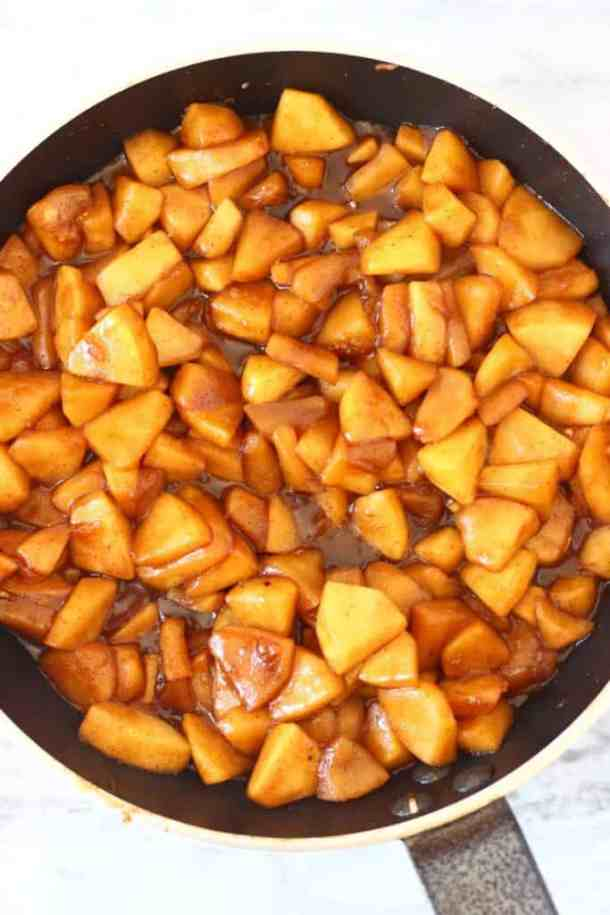 Photo of chopped apple pieces with cinnamon and brown sugar in a black frying pan
