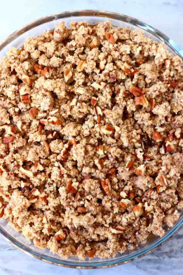 Photo of a raw apple crumble topped with chopped pecan nuts in a glass dish against a marble background