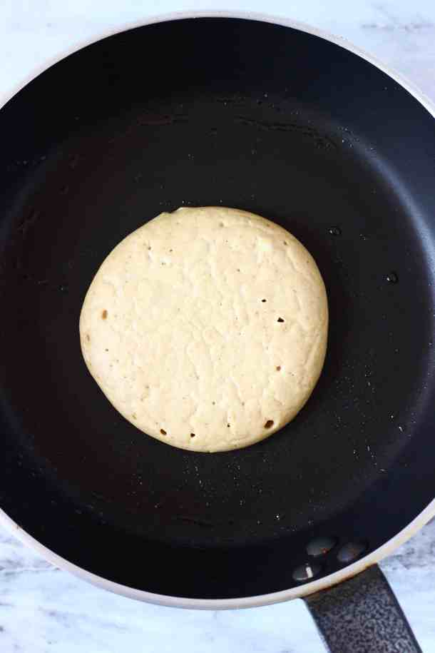Photo of an uncooked pancake batter in a black frying pan