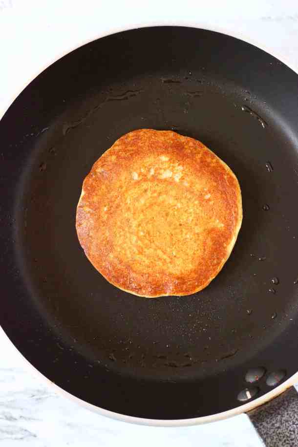 Photo of a golden brown pancake in a black frying pan