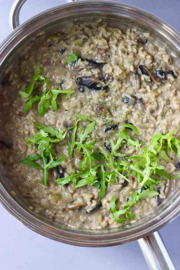 Mushroom risotto topped with rocket in a silver pan against a grey background