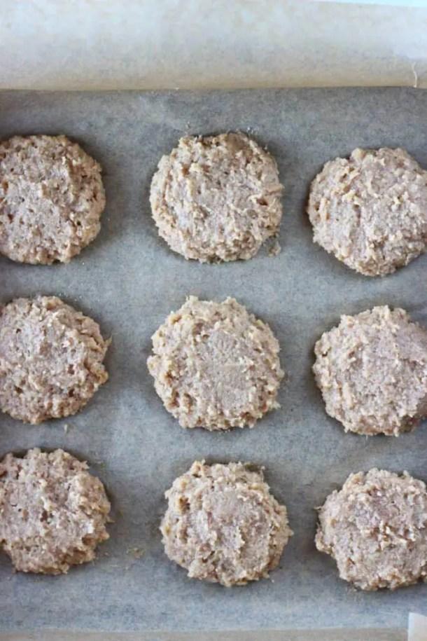 Nine raw brown cookies on a sheet of brown baking paper