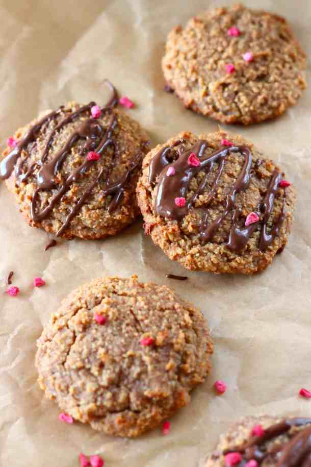Four golden brown cookies on a sheet of brown baking paper with two drizzled with melted dark chocolate and sprinkled with freeze-dried raspberries