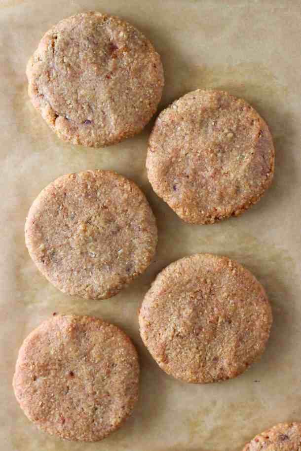 Five golden brown almond butter cookies on a sheet of brown baking paper