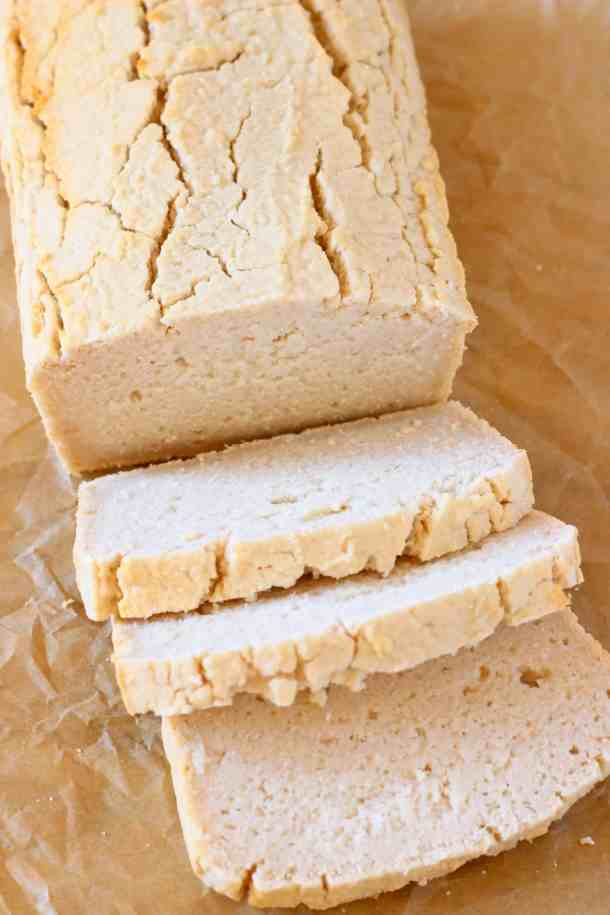A loaf of white bread with three slices against a sheet of brown baking paper