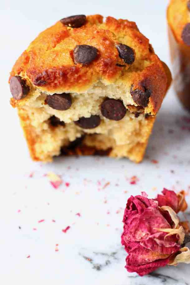 Half of a chocolate chip muffin on a marble slab with a dried rose