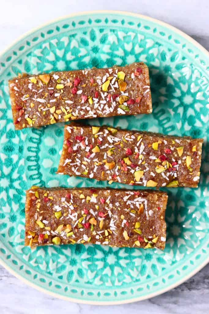 Three brown energy bars sprinkled with chopped pistachio nuts, desiccated coconut and freeze-dried raspberries against a green plate on a marble background