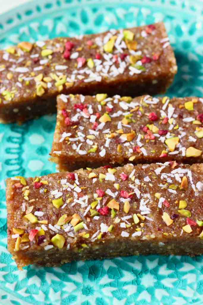 Three brown energy bars sprinkled with chopped pistachio nuts, desiccated coconut and freeze-dried raspberries against a green plate