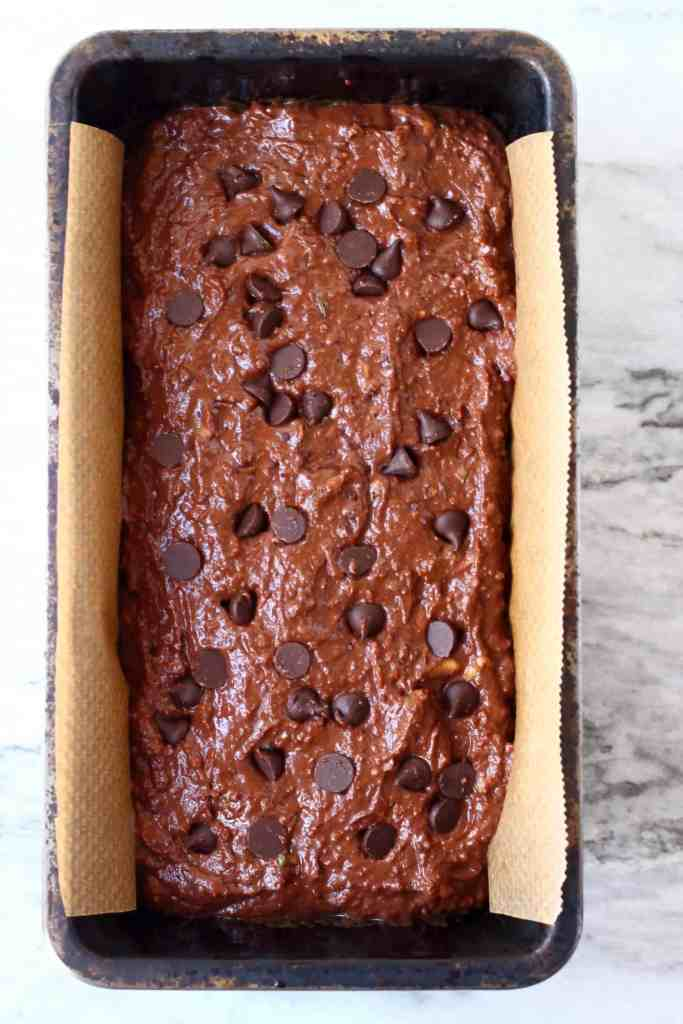 A loaf of raw chocolate zucchini bread batter studded with chocolate chips in a black loaf tin against a marble background