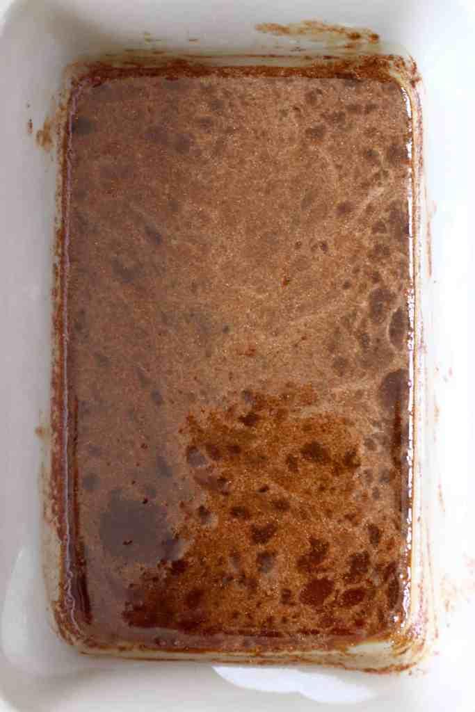 Dark brown caramel sauce for baked apples in a rectangular grey baking dish