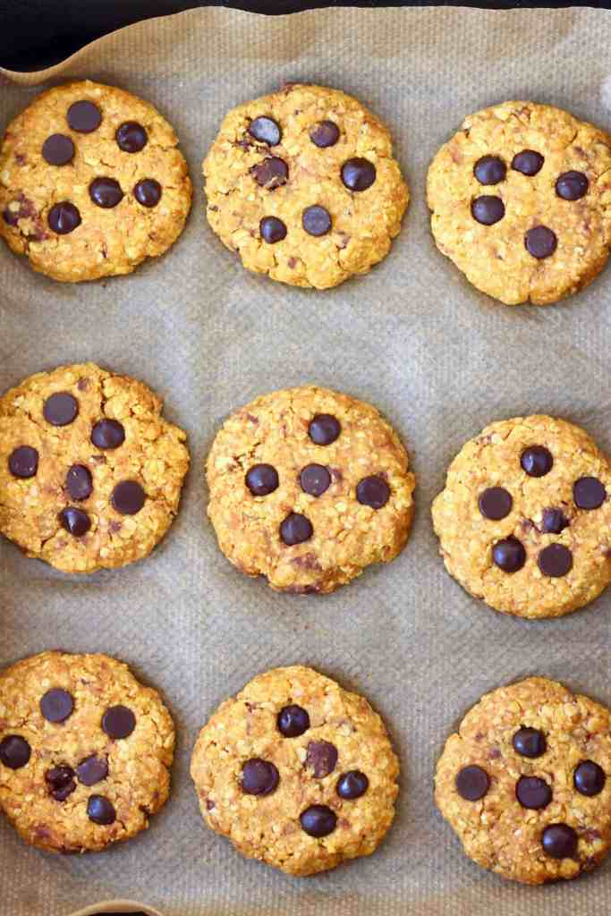 Nine raw pumpkin cookies studded with chocolate chips on a sheet of brown baking paper in a black baking tray