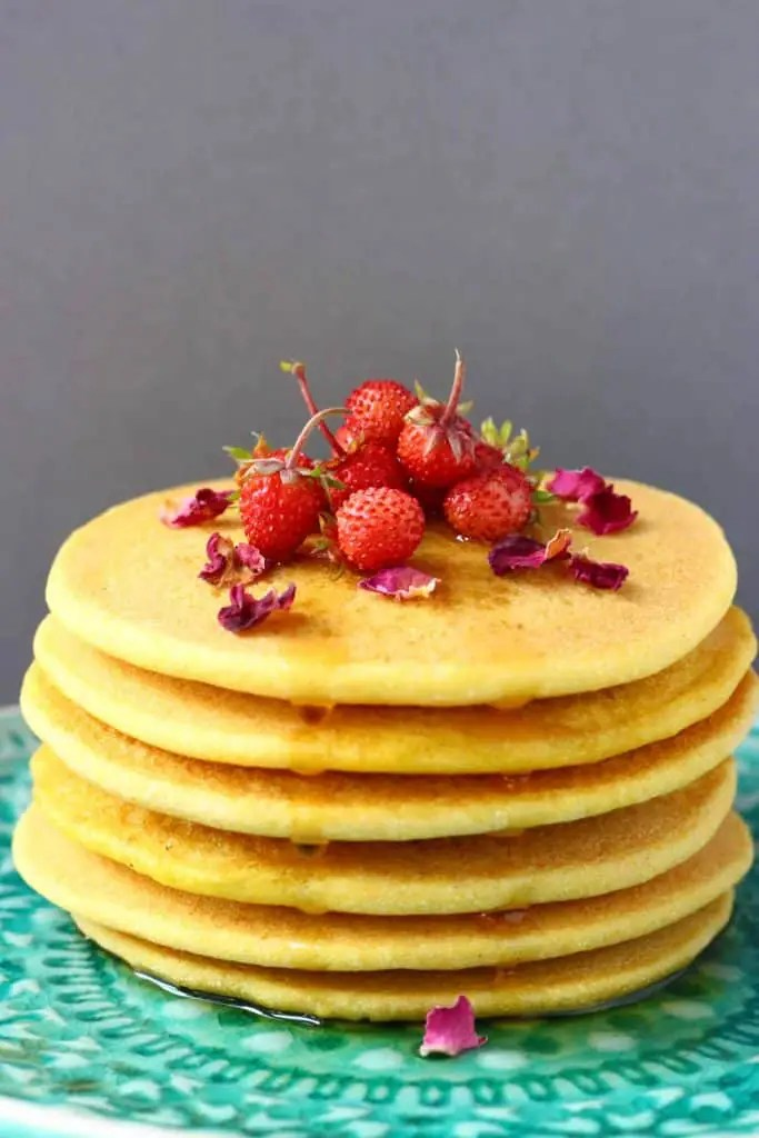 A stack of six yellow cornmeal pancakes topped with mini strawberries and rose petals on a green plate against a grey background