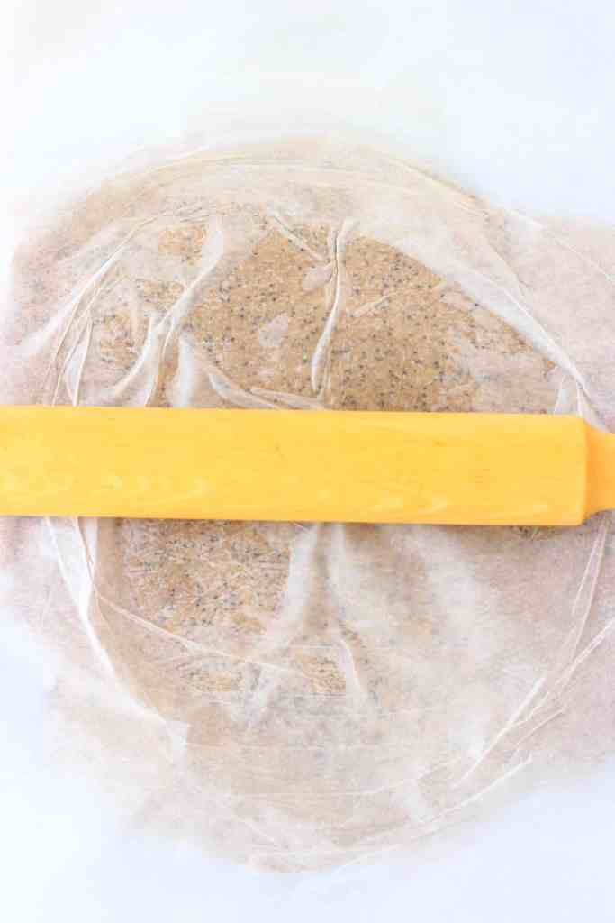 Cracker mixture between white baking paper rolled out with a rolling pin