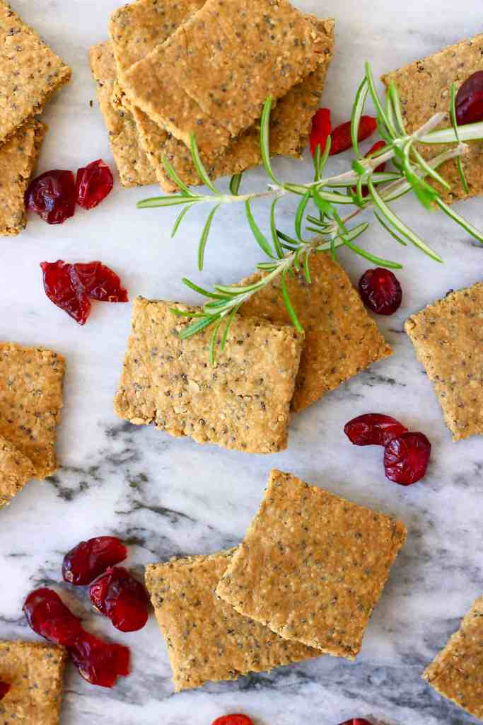 Several brown square crackers and dried cranberries against a marble background