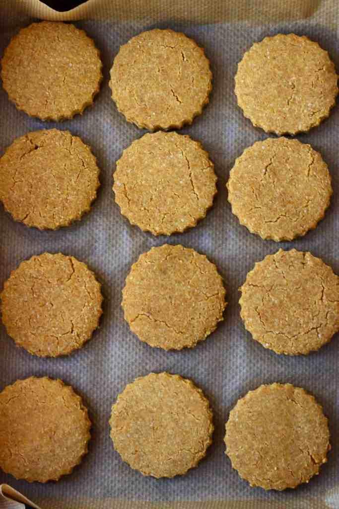 Twelve pumpkin cookies on a baking tray