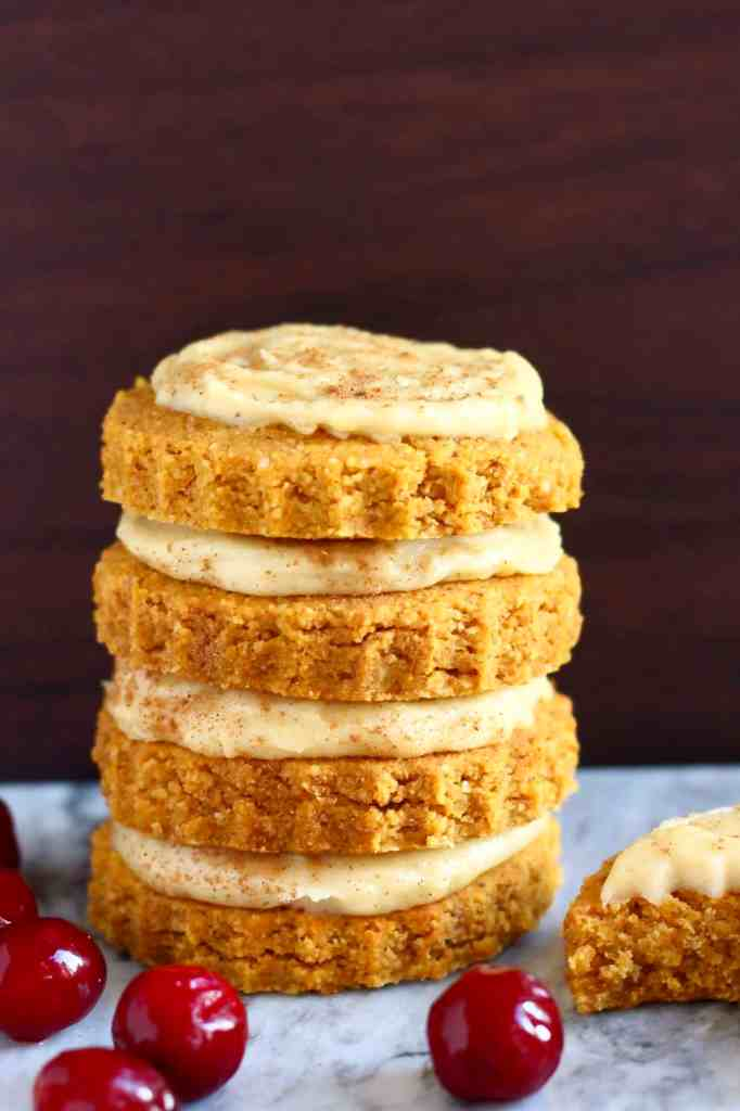 A stack of four pumpkin cookies topped with white frosting