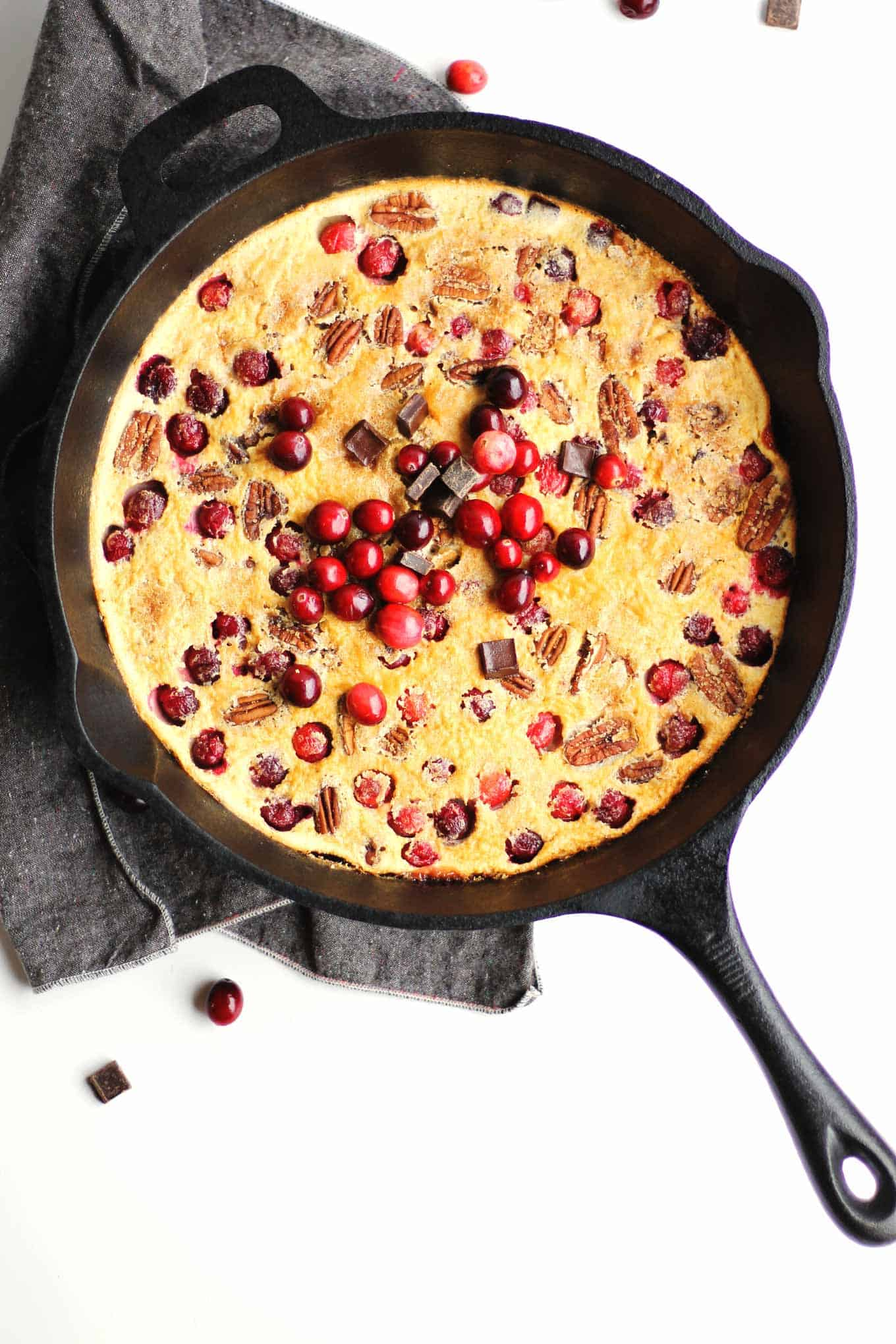 Cranberry clafoutis with dark chocolate and pecans! Easy blender recipe for the classic French custardy breakfast, with a holiday spin. Eat dessert for breakfast! - Rhubarbarians