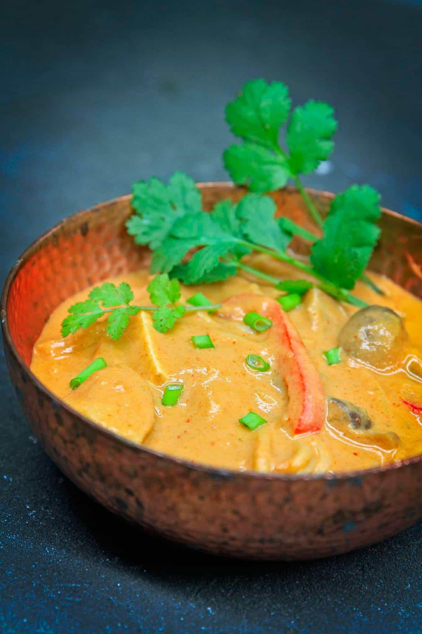 vegan thai peanut soup in a red bowl
