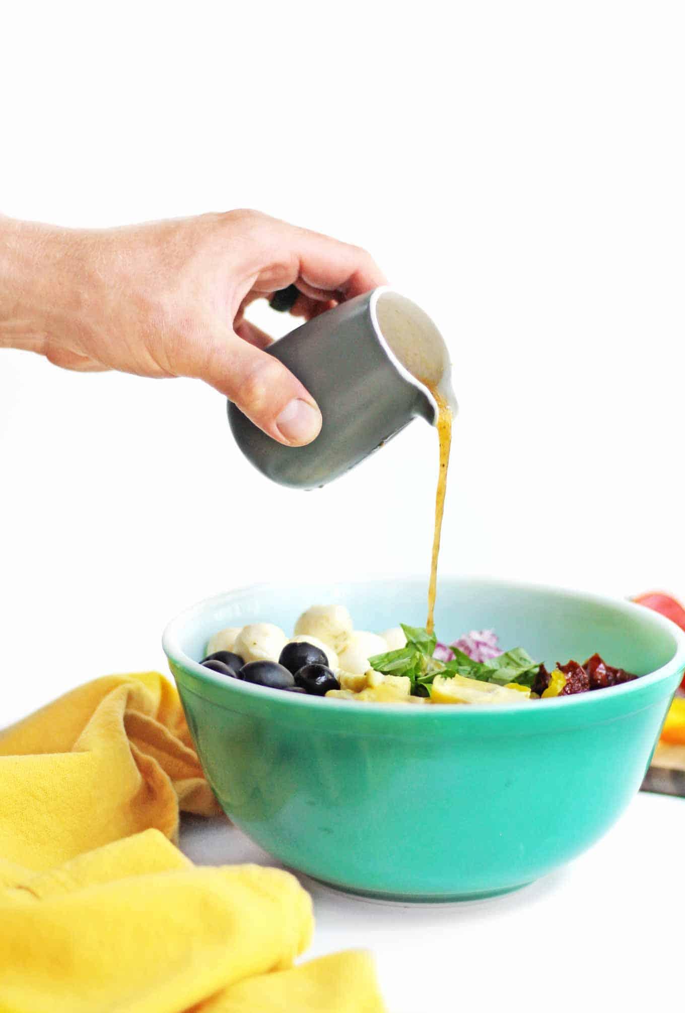Pouring dressing onto pasta salad