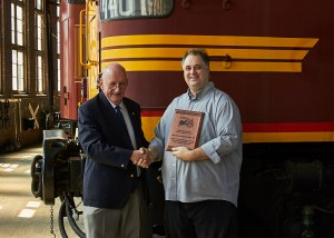 Nicholas Pyers, President of Junee Rhythm and Rail Inc, displaying the commemorative plaque as he presents it to The Hon. Tim Fischer AC, Patron of the Junee Rhythm n Rail Festival.