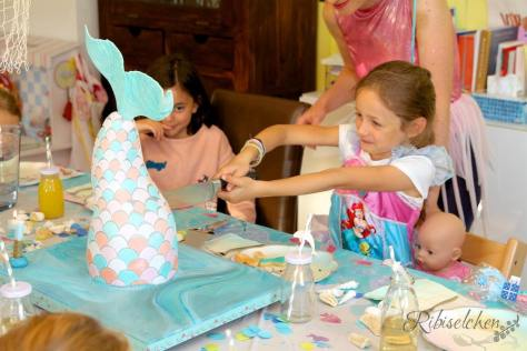 Geburtstagskind schneidet die Meerjungfrauentorte an