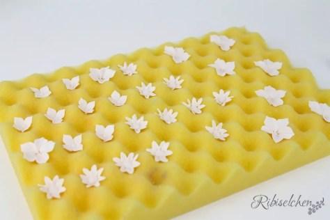 kleine Zuckerblüten aus Blütenpaste auf Schaumstoff