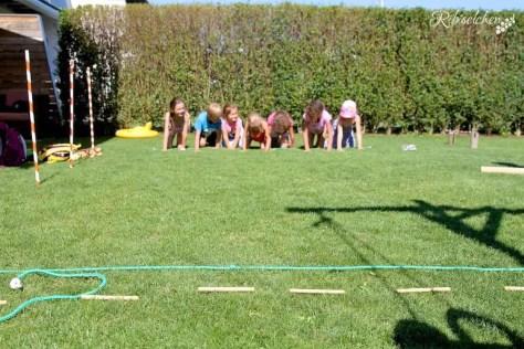 Kinder krabbeln auf der Wiese bei der Hundeparty