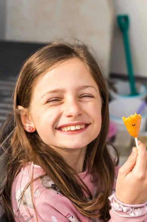 Kind mit angebissenem Cake Pop in der Hand