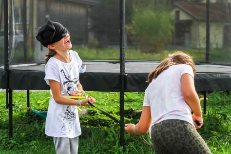 Kind wird mit verbundenen Augen an einer Leine von einem anderen Kind geführt beim Partyspiel Alpakawanderung