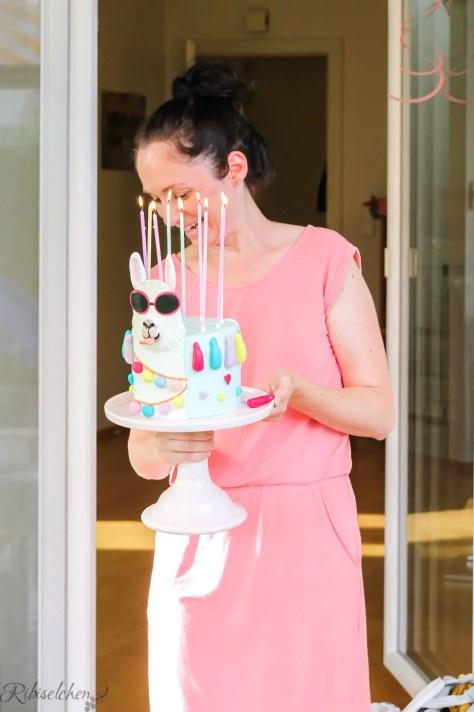 Mama trägt die Lama Torte mit angezündeten Kerzen