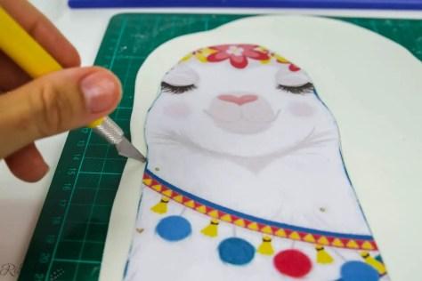 Lama Papiervorlage liegt auf Fondant und wird mit einem Skalpell ausgeschnitten