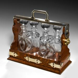 ANTIQUE OAK TANTALUS WITH FOUR DECANTERS