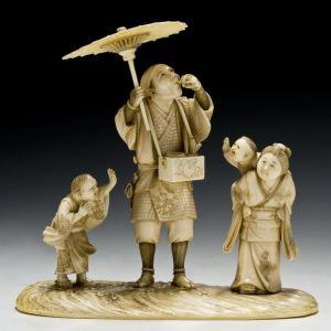 JAPANESE IVORY OKIMONO OF AN ENTERTAINER
