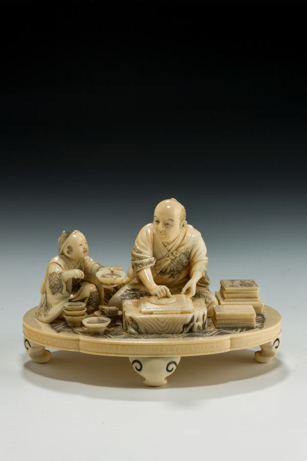 ANTIQUE JAPANESE IVORY OKIMONO OF A WOODBLOCK PRINTER