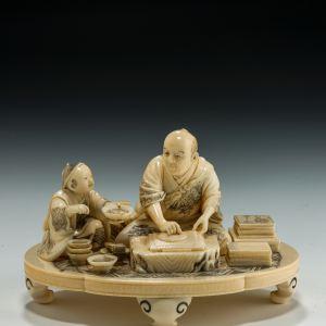 ANTIQUE JAPANESE IVORY OKIMONO OF A WOODBLOCK PRINTER