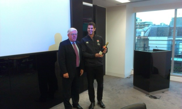 Toby Jones of the Rugby Football Union receives a bottle of champagne