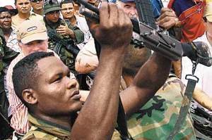 An AUC combatant handing over his weapon courtesy of El Espectador